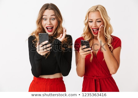 Portrait of two excited young smartly dressed women Stock photo © deandrobot