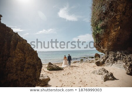 Couple holding hands on the beach of an exotic island during summer vacation Stock photo © Kzenon