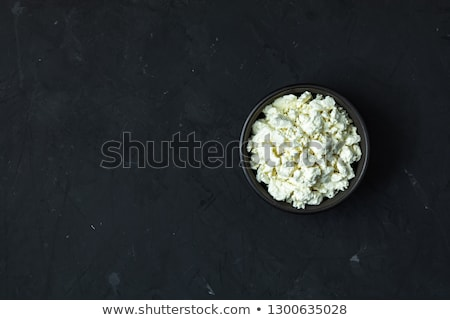 Stock photo: Homemade cottage cheese in a black ceramic bowl on dark concrete