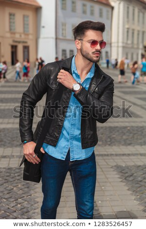 portrait of curious casual man holding shoulder bag relaxing Stock photo © feedough