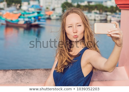 beautiful young cheerful woman taking a selfie against the background of the sea and vietnamese boat stock photo © galitskaya