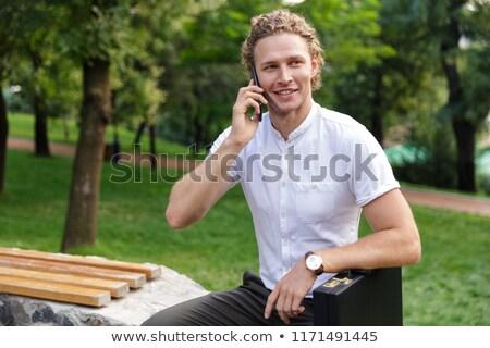 Derűs fürtös üzletember aktatáska beszél okostelefon Stock fotó © deandrobot