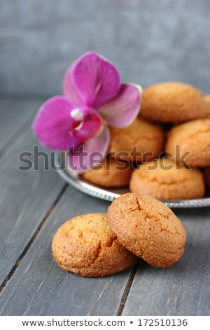Almond cookies with sugar tongs and orchid flower on rustic wooden table Stock photo © Melnyk