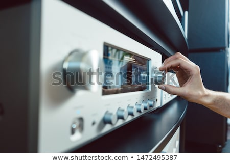 Hand of woman turning up volume of Hi-Fi amplifier Stock photo © Kzenon
