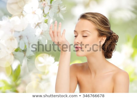 happy woman with perfume over cherry blossoms stock photo © dolgachov