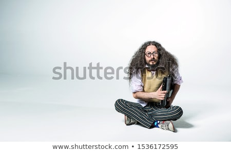 Portrait of a nerdy guy holding a briefcase and sitting on white Stock photo © majdansky