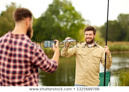 friend photographing fisherman with fish at lake Stock photo © dolgachov