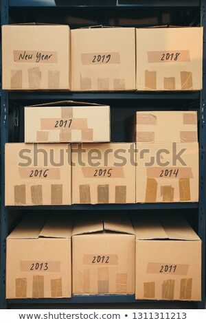 Cardboard boxes labeled number of years on shelves Stock photo © przemekklos