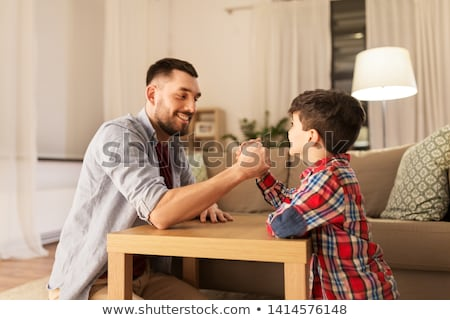 happy father and little son arm wrestling at home Stock photo © dolgachov