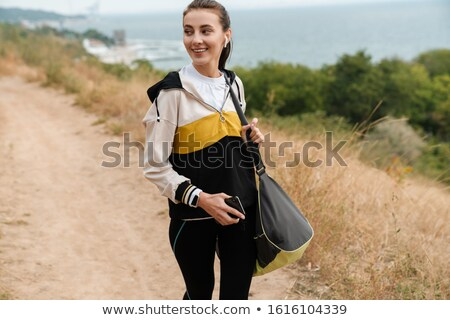 Photo of smiling woman using earpods and cellphone while working Stock photo © deandrobot