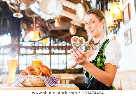 young woman in bavarian dress showing a glass with beer stock photo © rob_stark