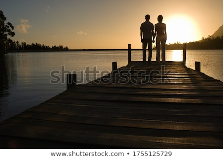 Stock photo: couple in love back light silhouette at lake sunset