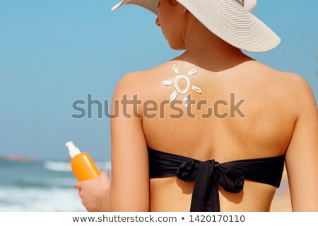 a woman drawing a face on her back with suntan lotion Stock photo © photography33