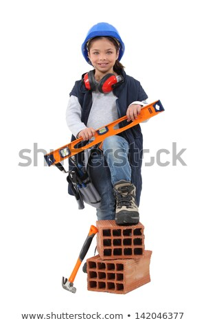 a little girl dressed in mason is taking a level and putting a foot on bricks stock photo © photography33