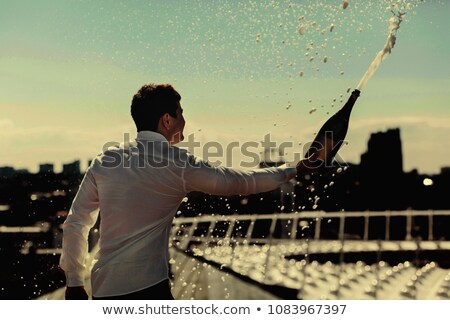 Young man opening a bottle of champagne Stock photo © photography33