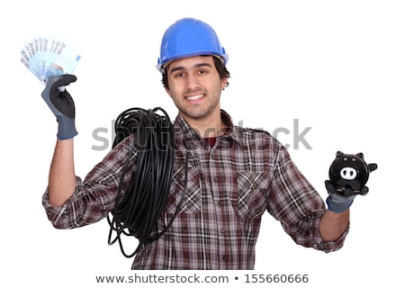 Stock photo: Laborer holding bills and piggy bank