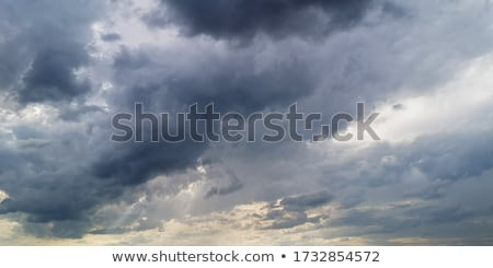 Panorama - sunbeams in stormy dark cloudy sky Stock photo © pzaxe
