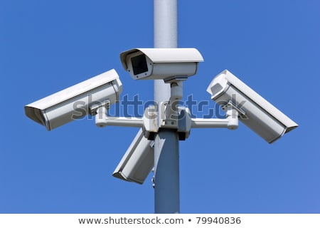 Stock photo: four security cameras on blue sky