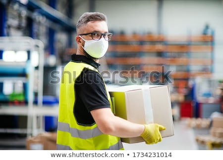 Stock fotó: Man Carrying Boxes In Warehouse