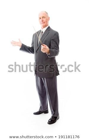 businessman holding a conductors baton stock photo © bmonteny