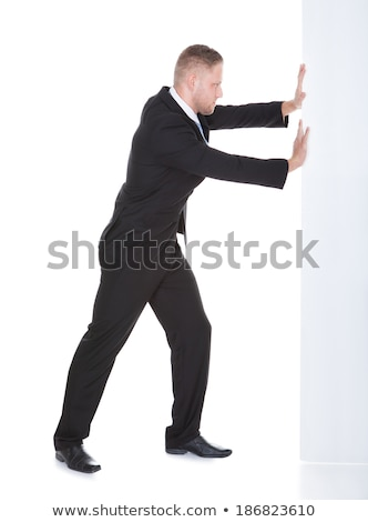 Businessman pushing the edge of a blank white sign Stock photo © AndreyPopov