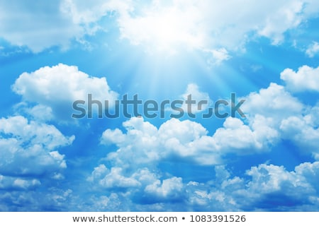 Deep Blue Sky and Puffy Clouds With Sun Rays stock photo © feverpitch