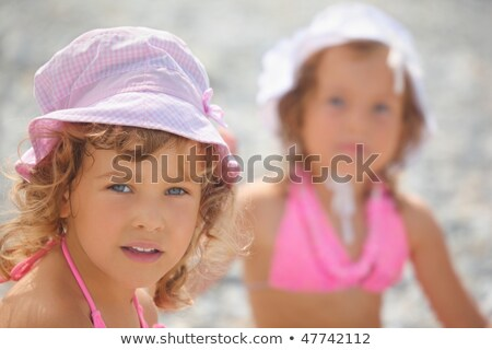 Two little girls on a sea coast. focus on girl wearing pink panama hat. another girl in out of focus Stock photo © Paha_L