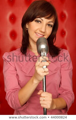 Portrait of girl in red shirt with microphone on rack against red wall. Vertical format. Stock photo © Paha_L