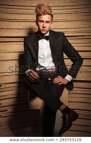 successful elegant man in tuxedo and bowtie sitting on stool  Stock photo © feedough