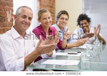 Four businesspeople in boardroom applauding and smiling Stock photo © monkey_business