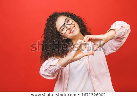 pretty smiling girl showing heart gesture with two hands stock photo © deandrobot