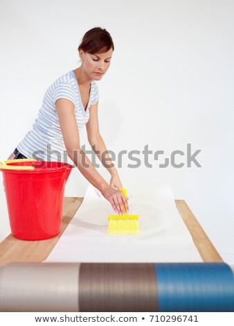 Woman brushing paste onto wallpaper Stock photo © IS2