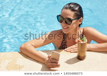 Woman relaxing with drink in hotel pool Stock photo © IS2