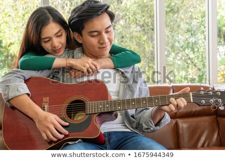 young couple playing guitar in the room stock photo © boggy
