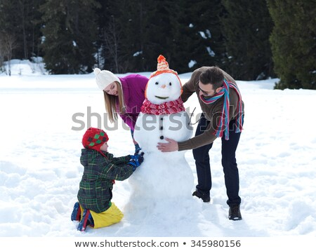 a girl building snowman on white background stock photo © bluering