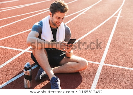 Smiling sportsman finished running at the stadium, resting Stock photo © deandrobot