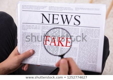 Man Examining Fake News On Newspaper Stock photo © AndreyPopov