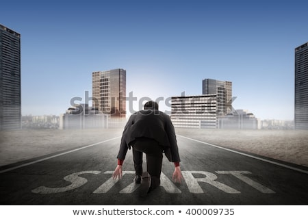Businessman kneeling in ready position Stock photo © ra2studio