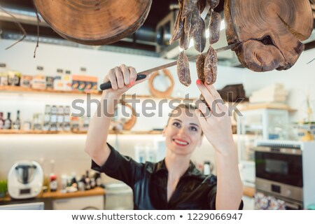 Sales clerk in deli cutting sausages to sell them Stock photo © Kzenon
