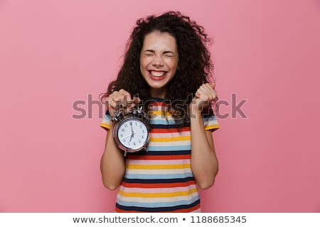 photo of uptight woman 20s with curly hair holding alarm clock stock photo © deandrobot