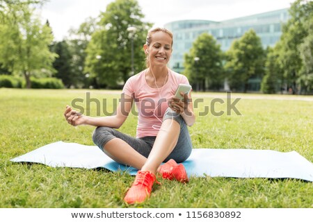 woman with smartphone setting music for meditation Stock photo © dolgachov