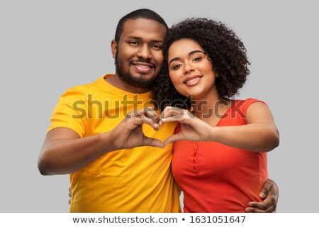 Woman isolated over grey background showing heart love gesture. Stock photo © deandrobot