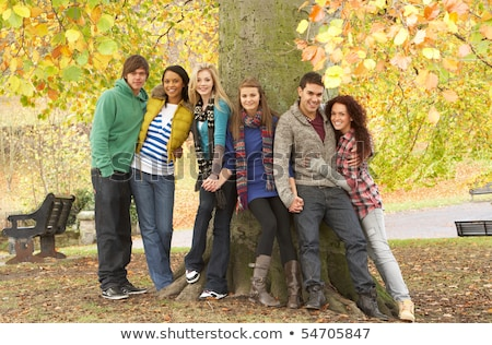 group of six teenage friends leaning against tree in autumn park stock photo © monkey_business