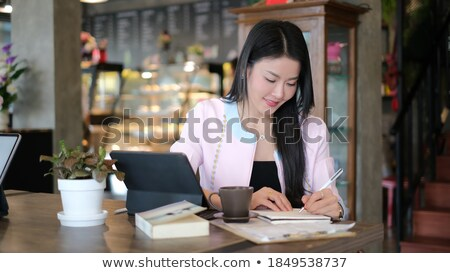Young businesswoman making notes in notebook while watching webinar Stock photo © pressmaster