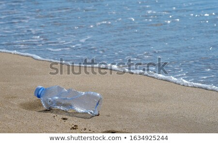 Copy space of empty garbage bottles on sand beach texture background. Nature and environment concept Stock photo © galitskaya