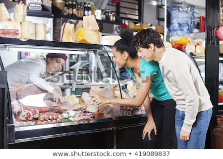 Сток-фото: Shop Assistant Women Selling Cheese And Meats In Deli