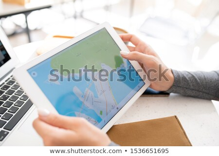 Hands of young female student holding digital tablet with map on display Stock photo © pressmaster