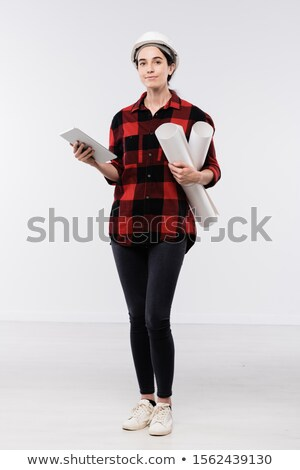 Pretty young female architect in hardhat, flannel and leggins using touchpad Stock photo © pressmaster