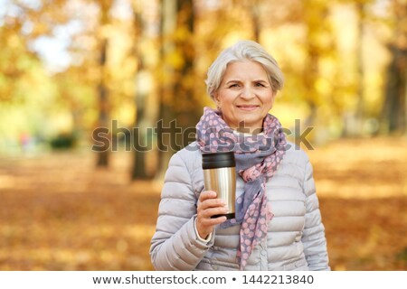 old woman with hot drink in tumbler at autumn park Stock photo © dolgachov