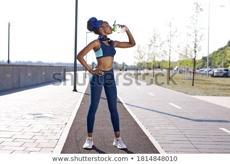 Female with water after workout Stock photo © phakimata